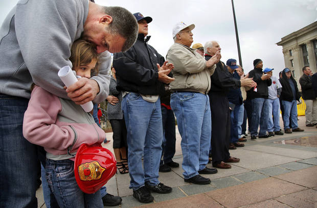 Moore Fire Department Cpl. Kevin Goodnight leans down to hug his daughter, Gabriella, 8, as the two listened to speakers during the rally. An estimated 400 active and retired firefighters from across Oklahoma rallied on the south plaza of the state Capitol Monday morning, March 18, 2013, before going inside the building to visit with lawmakers and voice their concerns about proposed changes in pension and workers' compensation systems.      Photo by Jim Beckel, The Oklahoman <strong>Jim Beckel - THE OKLAHOMAN</strong>