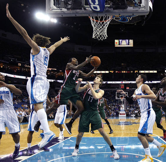 Milwaukee Bucks guard Brandon Jennings (3) drives to the basket between forward Mike Dunleavy (17), New Orleans Hornets center Robin Lopez (15), and guard Austin Rivers (25) in the first half of an NBA basketball game in New Orleans, Monday, Dec. 3, 2012. (AP Photo/Gerald Herbert)