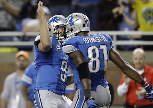Detroit Lions quarterback Matthew Stafford (9) congratulates teammate Calvin Johnson after Johnson scored on a 46-yard reception during the third quarter of an NFL football game against the Indianapolis Colts at Ford Field in Detroit, Sunday, Dec. 2, 2012. (AP Photo/Paul Sancya)