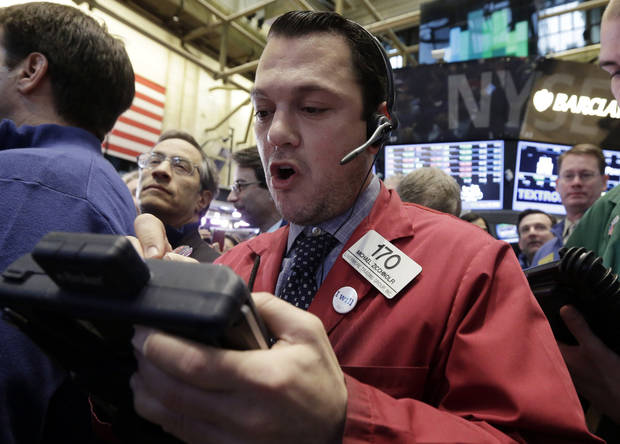 Trader Michael Zicchinolfi, center, works on the floor of the New York Stock Exchange, Friday, Jan. 25, 2013. Stocks are opening higher on Wall Street ahead of what is expected to be more upbeat data on housing from the government. (AP Photo/Richard Drew)