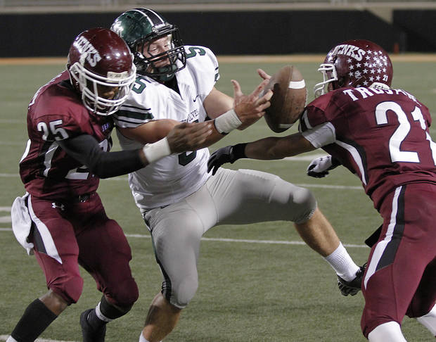Jenks' Durelle Davis (25) Austin Casillas (21) force a fumble on Norman North's Beau Proctor (5) during the Class 6A Oklahoma state championship football game between Norman North High School and Jenks High School at Boone Pickens Stadium on Friday, Nov. 30, 2012, in Stillwater, Okla.   Photo by Chris Landsberger, The Oklahoman