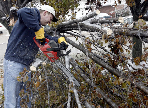 WINTER / COLD / WEATHER / ICE STORM / DAMAGE / CLEAN UP / CLEANUP / AFTERMATH: Tim Griffin cuts trees up that fell in his yard in the Smiling Hills neighbood on Monday December 10, 2007, in Edmond, Okla. By Sarah Phipps, The Oklahoman  ORG XMIT: KOD