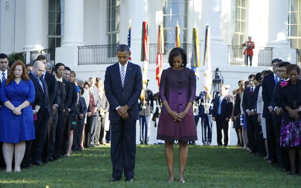 President Barack Obama first lady Michelle Obama, and members of the White House staff pause during a moment of silence to mark the 11th anniversary of the Sept, 11th, Tuesday, Sept. 11, 2012, on the South Lawn of the White House in Washington. (AP Photo/Carolyn Kaster)