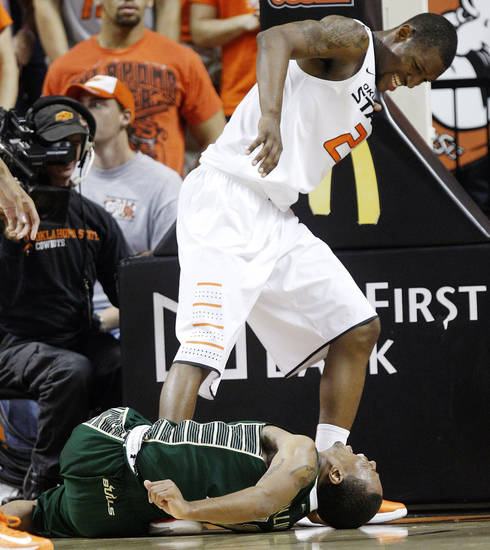 South Florida's Anthony Collins, bottom, grimaces after a foul by Oklahoma State forward Kamari Murphy, top, in the first half of an NCAA college basketball game in Stillwater, Okla., Wednesday, Dec. 5, 2012. (AP Photo/Sue Ogrocki)