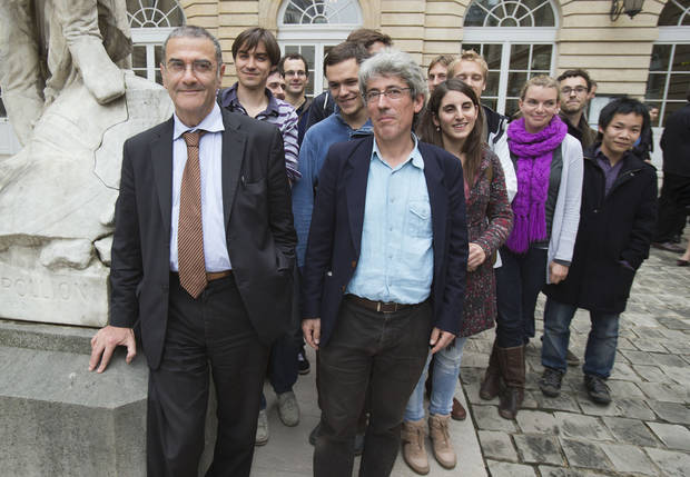 Serge Haroche of France, left, winner of the 2012 Nobel Prize in physics, poses with his research team at the College de France in Paris, Tuesday, Oct. 9, 2012. Haroche and American David Wineland shared the 2012 Nobel Prize in physics Tuesday for inventing methods to observe the bizarre properties of the quantum world, research that has led to the construction of extremely precise clocks and helped scientists take the first steps toward building superfast computers. (AP Photo/Michel Euler)