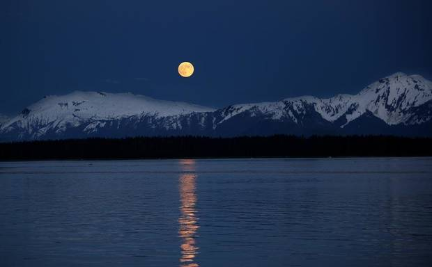 A full moon rises over a mountain range near Tracy Arm in Alaska