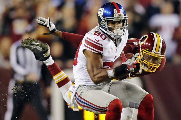New York Giants wide receiver Victor Cruz (80) pulls in a pass under pressure from Washington Redskins defensive back Cedric Griffin during the first half of an NFL football game in Landover, Md., Monday, Dec. 3, 2012. (AP Photo/Evan Vucci)