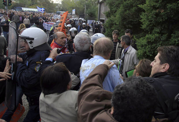 A protester with the brown jacket punches the German consul in Thessaloniki, Wolfgang Hoelsche-Obermaier, center with the blue shirt, who arrives to attend a conference of Greek and German mayors as police and organizers try to protect him in the northern Greek port city of Thessaloniki, Thursday, Nov. 15, 2012. Dozens of anti-austerity protesters broke into a conference and clashed with police to demonstrate against the presence of a German government official. (AP Photo/Nikolas Giakoumidis)