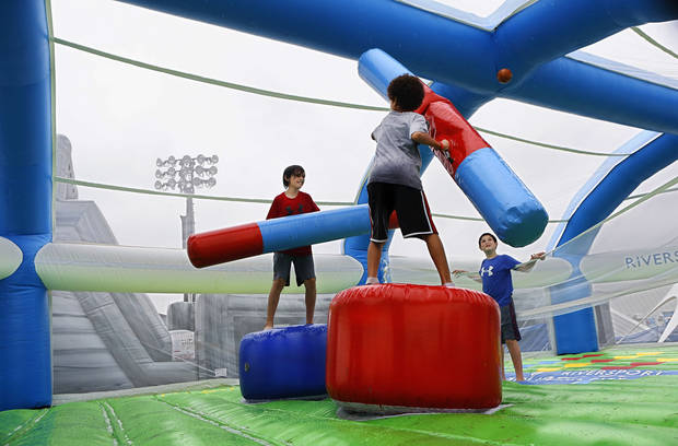 Boys test each other's fighting skills in an inflatable battlefield. Regatta Festival on the Oklahoma River in the Boat District,  Saturday,  Sep. 29, 2012. The event ends Sunday. Photo by Jim Beckel, The Oklahoman.