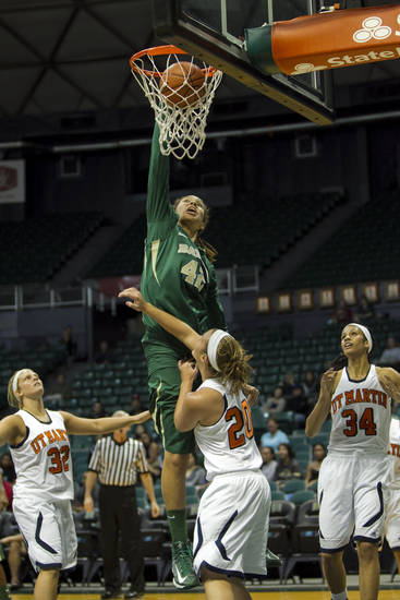 Baylor center Brittney Griner (42), center, dunks the ball over Tennessee-Martin players Megan White (32), Katie Schubert (20), and Shelby Crawford (34) during the first half of the NCAA college basketball game Saturday, Nov. 17, 2012 in Honolulu. (AP Photo/Marco Garcia)