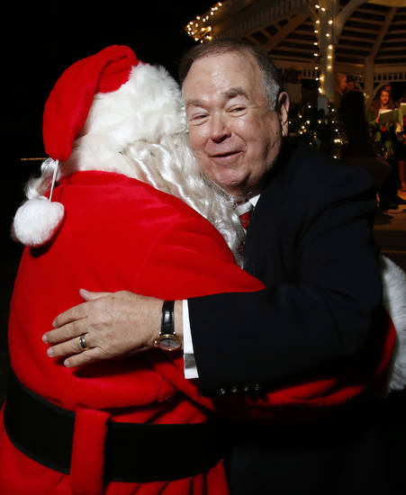 University of Oklahoma President David Boren gets a hug from Santa Claus at OU&acirc;s holiday lights celebration. PHOTOs BY STEVE SISNEY, THE OKLAHOMAN