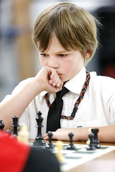 Ashton Pavao, a third grader, studies a chess move during a chess club meeting at Freeman Elementary School in Edmond. Photo By Steve Gooch, The Oklahoman <strong>Steve Gooch - The Oklahoman</strong>