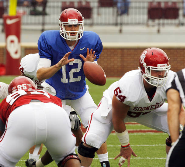 SPRING FOOTBALL / COLLEGE FOOTBALL: Landry Jones (12) takes a snap from Gabe Ikard (64) during the University of Oklahoma (OU) football team's annual Red and White Game at Gaylord Family - Oklahoma Memorial Stadium on Saturday, April 14, 2012, in Norman, Okla.  Photo by Steve Sisney, The Oklahoman