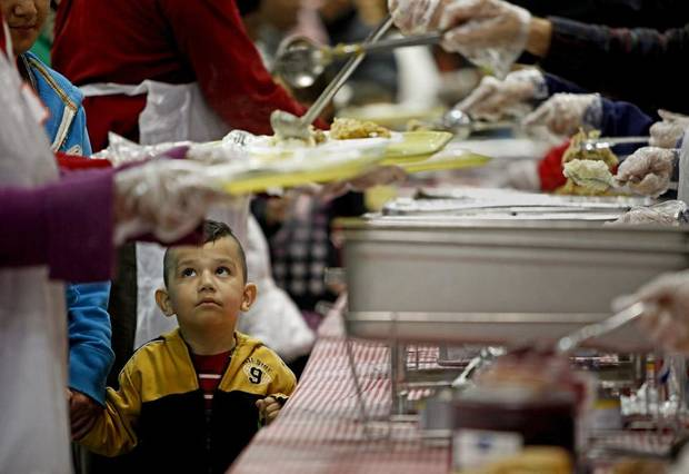 CHILD / CHILDREN / KIDS: Three-year-old Alejandro Sanchez watches as his plate is filled during the annual Red Andrews Christmas Dinner at the Cox Convention Center in Oklahoma City, Saturday, Dec. 25, 2010.  Photo by Bryan Terry, The Oklahoman ORG XMIT: KOD