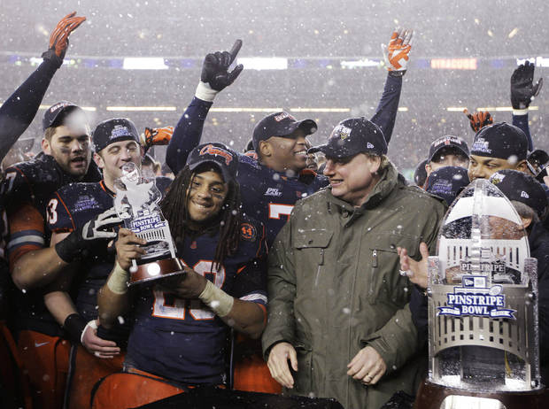 New York Yankees president Randy Levine, center right, smiles after presenting Syracuse running back Prince-Tyson Gulley (23) with the Most Valuable Player trophy after the Pinstripe Bowl NCAA college football game at Yankee Stadium in New York, Saturday, Dec. 29, 2012. Syracuse defeated West Virginia 38-14. (AP Photo/Kathy Willens)