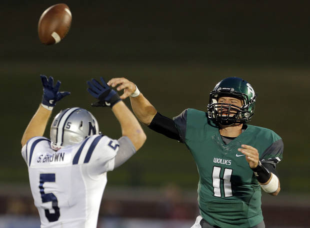 Edmond Santa Fe's Justice Hansen throws the ball as Edmond North's Sam Brown defends during high school football game between Edmond Santa Fe and Edmond North at Wantland Stadium in Edmond, Okla.,  Friday, Sept. 14, 2012. Photo by Sarah Phipps, The Oklahoman