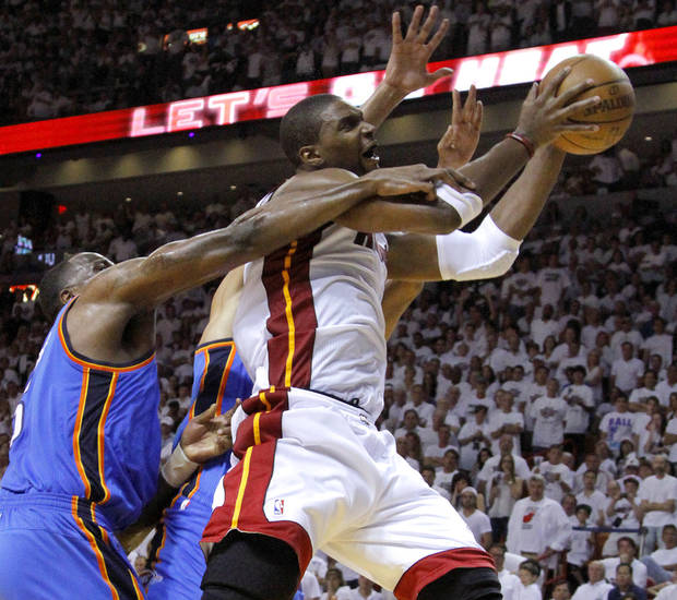 Miami's Chris Bosh (1) is fouled by Oklahoma City's Kendrick Perkins (5) during Game 3 of the NBA Finals between the Oklahoma City Thunder and the Miami Heat at American Airlines Arena, Sunday, June 17, 2012. Photo by Bryan Terry, The Oklahoman