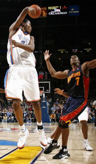 Oklahoma City's Kevin Durant passes the ball over his shoulder past Kelenna Azubuike of Golden State in the first half during the NBA basketball game between the Golden State Warriors and the Oklahoma City Thunder at the Ford Center in Oklahoma City, Monday, December 8, 2008. BY NATE BILLINGS, THE OKLAHOMAN