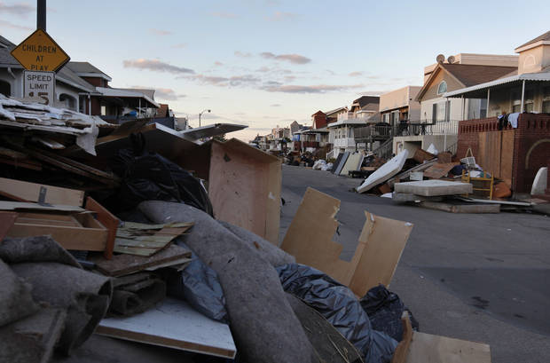 In this Monday, Nov. 5, 2012, photo, items discarded from homes damaged by Superstorm Sandy line a street, in Long Beach, N.Y. Temperatures dipped toward freezing early Monday, and tens of thousands of people without power along the ravaged Atlantic coastline faced the prospect of finding somewhere else to stay. (AP Photo/Jason DeCrow)