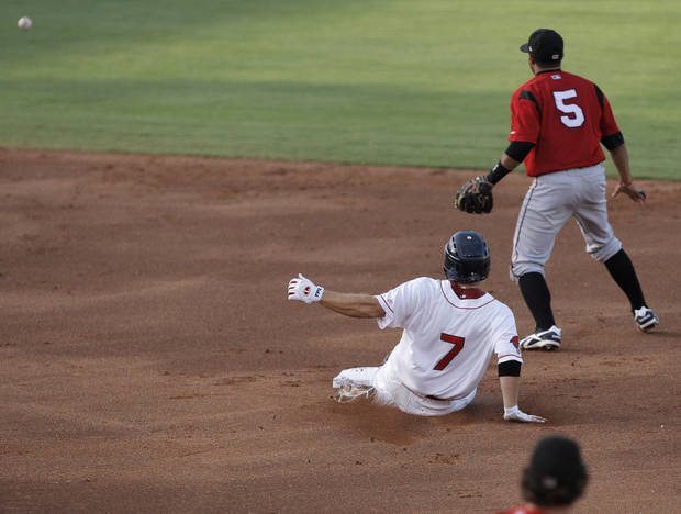 J.B. Shuck (7) slides into second base as a ball goes past Nashville's Eric Farris (5) during a game between the Oklahoma City Redhawks and the Nashville Sounds in Oklahoma City, Wednesday, July 27, 2011.  Photo by Garett Fisbeck, The Oklahoman ORG XMIT: KOD