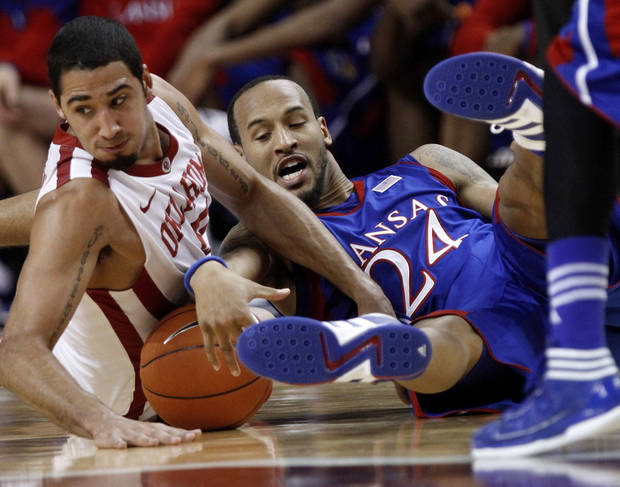 Oklahoma forward C.J. Washington, left, and Kansas guard Travis Releford (24) reach for the ball in the second half of an NCAA college basketball game in Norman, Okla., Saturday, Jan. 7, 2012. Kansas won 72-61. (AP Photo/Sue Ogrocki)