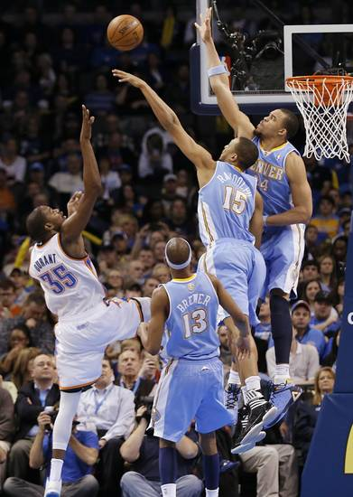 Oklahoma City's Kevin Durant (35) shoots over Denver's Anthony Randolph (15) and JaVale McGee (34) during the NBA basketball game between the Oklahoma City Thunder and the Denver Nuggets at the Chesapeake Energy Arena on Wednesday, Jan. 16, 2013, in Oklahoma City, Okla.  Photo by Chris Landsberger, The Oklahoman