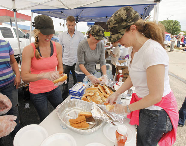 Alana Palmer, left, Marlo Robertson, and Kellie Wostal, with the ADT company, prepare free hot dogs for residents and workers on the north perimeter of the tornado devastated part of Moore, OK, Thursday, May 23, 2013,  Photo by Paul Hellstern, The Oklahoman
