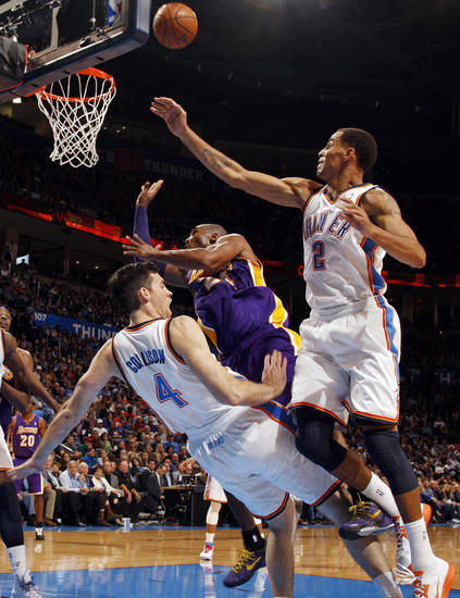 Oklahoma City's Nick Collison (4) takes a charge from Los Angeles' Kobe Bryant (24) next to Oklahoma City's Kendrick Perkins (5) during an NBA basketball game between the Oklahoma City Thunder and the Los Angeles Lakers at Chesapeake Energy Arena in Oklahoma City, Friday, Dec. 7, 2012. Oklahoma City won, 114-108. Photo by Nate Billings, The Oklahoman