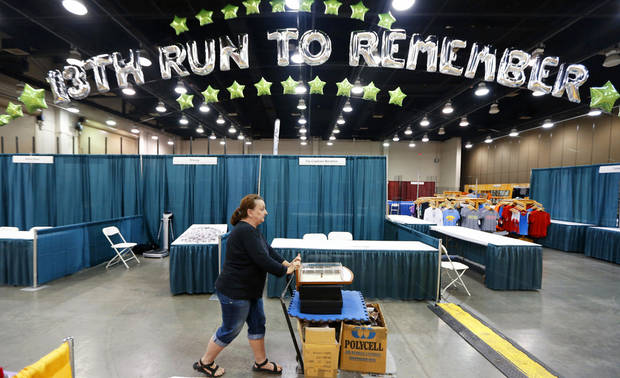 Julie Tuchscher pushes a cart loaded with sunglasses Thursday at the Cox Convention Center in preparation for the Oklahoma City Memorial Marathon.  Photos By Steve Gooch, The Oklahoman