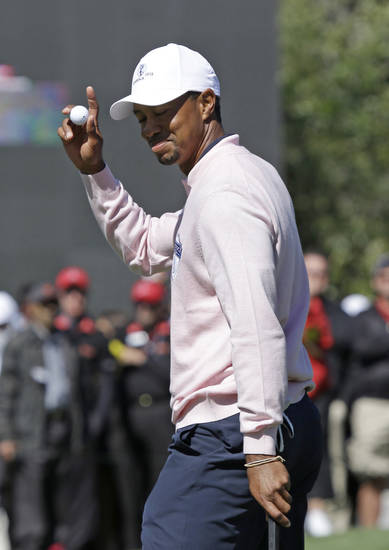 Tiger Woods waves to the gallery after his putt on the 18th green during the Tavistock Cup golf tournament, Tuesday, March 26, 2013, in Windermere, Fla. (AP Photo/John Raoux)