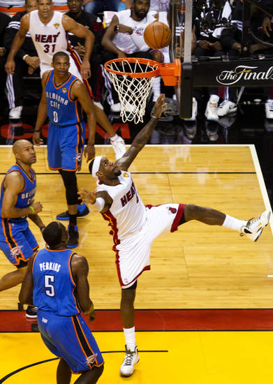 Miami Heat's LeBron James, center, shoots past Oklahoma City Thunder's Kendrick Perkins (5), Derek Fisher, left, and Russell Westbrook (0) in the first quarter of Game 3 of the NBA Finals basketball series, Sunday, June 17, 2012, in Miami. (AP Photo/The Miami Herald, C.W. Griffin)  MAGS OUT ORG XMIT: FLMIH203