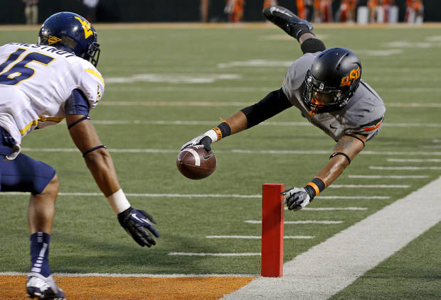 Oklahoma State's Josh Stewart (5) leaps for a touchdown as West Virginia's Terrell Chestnut (16) during a college football game between Oklahoma State University (OSU) and West Virginia University at Boone Pickens Stadium in Stillwater, Okla., Saturday, Nov. 10, 2012. Oklahoma State won 55-34. Photo by Bryan Terry, The Oklahoman