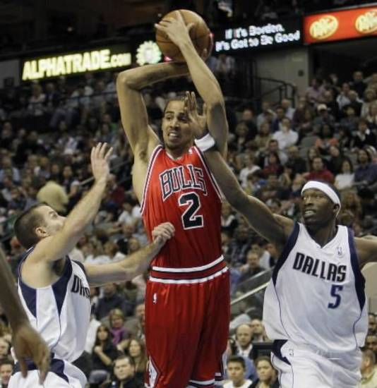 Chicago Bulls forward Thabo  Sefolosha, center, of Switzerland, looks to pass the ball between Dallas Mavericks guard Jose Juan Barea, left, of Puerto Rico, and forward Josh Howard during the first half of an NBA basketball game, Saturday, Feb. 7, 2009, in Dallas. (AP Photo/Matt Slocum)