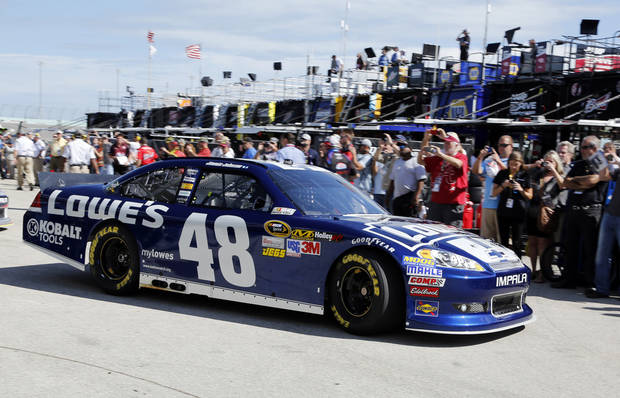 Fans line up to photograph Jimmie Johnson as he drives to practice for Sunday's NASCAR Sprint Cup Series auto race at Homestead-Miami Speedway Saturday, Nov. 17, 2012 in Homestead, Fla. The final Sprint Cup series race will take place Sunday. (AP Photo/Terry Renna)