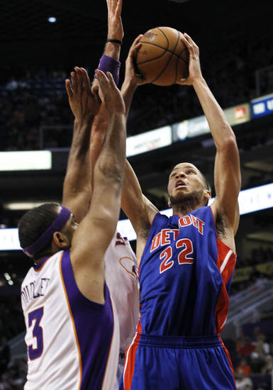 Detroit Pistons' Tayshaun Prince (22) tries to get off a shot as Phoenix Suns' Jared Dudley (3) and Marcin Gortat (obscured), of Poland, defend in the first half of an NBA basketball game on Friday, Nov. 2, 2012, in Phoenix. (AP Photo/Ross D. Franklin)