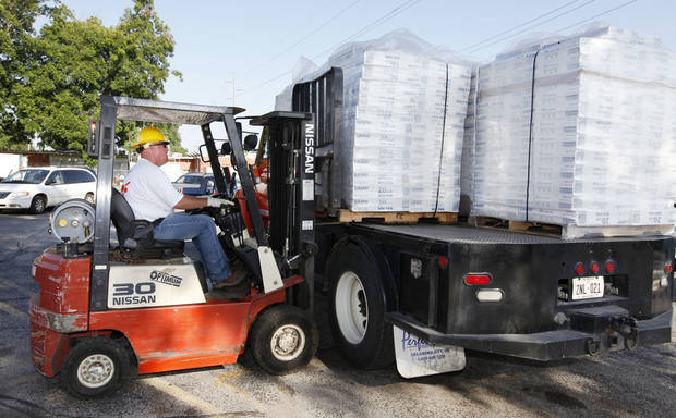Oklahoma Gas and Electric employee Tracy Kitchens uses a forklift to unload an OG&E truck loaded with 300 box fans being donated to the Salvation Army in Oklahoma City Thursday, June 20, 2013. Photo by Paul B. Southerland, The Oklahoman