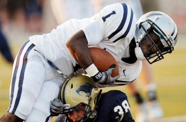 Edmond North's Jarion Tudman (1) pushes past Southmoore's Colton Shackelford (38) for a touchdown during a high school football game between Edmond North and Southmoore in Moore, Okla., Thursday, Sept. 1, 2011. Photo by Nate Billings, The Oklahoman