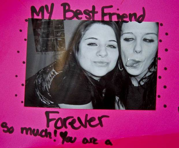 Photos of Carina Saunders, left, with Gabrielle McAllister brought by friends during a vigil during a vigil on Tuesday afternoon for Carina Saunders, whose body was found in a duffel bag last week behind a Bethany Homeland last week. <strong>CHRIS LANDSBERGER - CHRIS LANDSBERGER</strong>