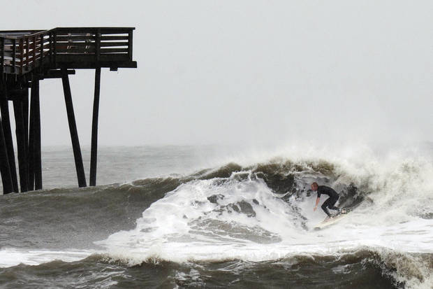 A surfer rides a wave at the Virginia Beach Fishing Pier at 15th Street, Monday, Oct. 29, 2012, in Virginia Beach, Va. Large waves were created as Hurricane Sandy continued on its path Monday, forcing the shutdown of mass transit, schools and financial markets, sending coastal residents fleeing for higher ground, and threatening a dangerous mix of high winds and soaking rain. (AP Photo/The Virginian-Pilot, L. Todd Spencer)  MAGS OUT ORG XMIT: VANOV402