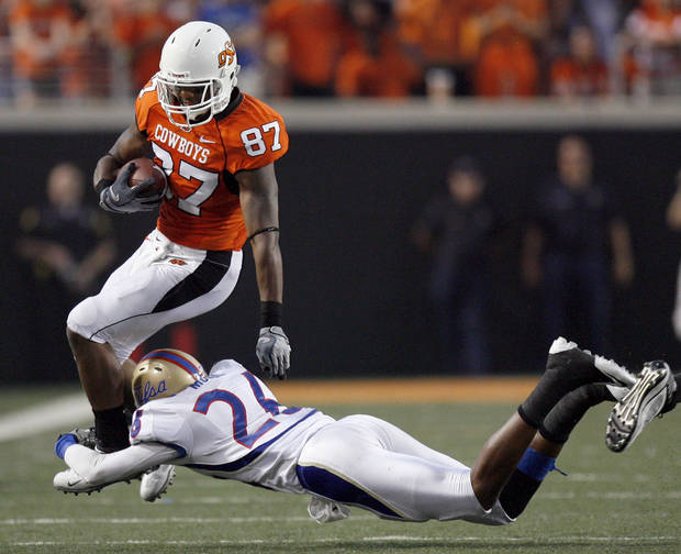 Oklahoma State wide receiver Tracy Moore (87) tries to get by Tulsa's Dexter McCoil (26) during the college football game between the University of Tulsa (TU) and Oklahoma State University (OSU) at Boone Pickens Stadium in Stillwater, Oklahoma, Saturday, September 18, 2010. Photo by Sarah Phipps, The Oklahoman