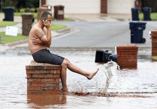 Daniel Parker splashes water Monday while sitting on his mailbox in front of his house in the Palo Verde Addition near Edmond after floodwaters inundated a number of homes in the area. photo By Paul Hellstern, The Oklahoman