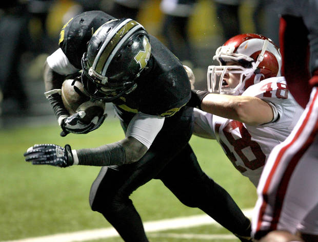 Midwest City running back James Flanders gets past Owasso tackler Ty McKenzie , crossing the goal line in the corner of the end zone for the Bombers' third touchdown. This was MWC's first score of the third quarter during Class 6A playoff game between Midwest City Bombers and the Owasso Rams at Jim Darnell Stadium in Midwest City, Friday night, Nov. 18, 2011.  Photo by Jim Beckel, The Oklahoman