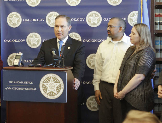 Attorney General Scott Pruitt holds a news conference Monday at his office in Oklahoma City with Zachary and Melissa Zuniga of Tulsa.  PHOTO BY PAUL HELLSTERN, THE OKLAHOMAN