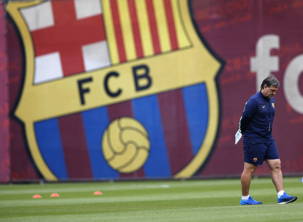 Barcelona FC's coach Gerardo Martino walks across the pitch during a training session with his team in Barcelona, Spain, Tuesday, Sept. 17, 2013, ahead of their Champions League group H soccer match against Ajax Amsterdam on Wednesday. (AP Photo/Emilio Morenatti)