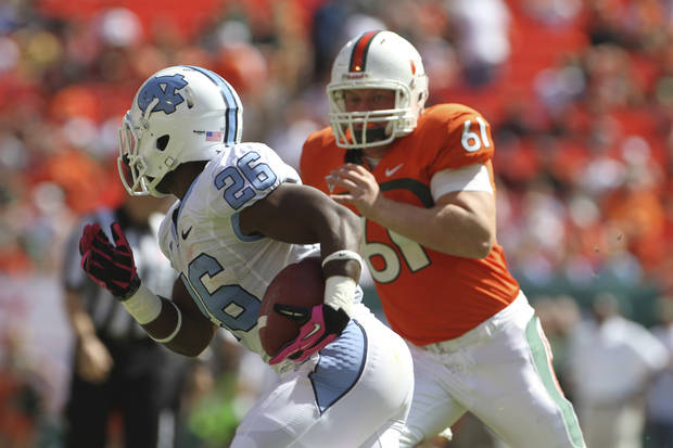 North Carolina's Giovani Bernard (26) out runs Miami's Paul Kelly (61) during the first half of a NCAA college football game in Miami, Saturday, Oct. 13, 2012. (AP Photo/J Pat Carter)