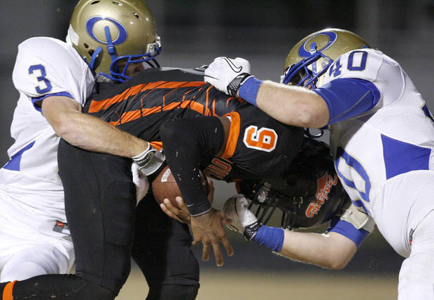 Douglass' Marcus Caddell is brought down by Oologah's Colton Sharp, left, and Dakota Hudgens during a high school football playoff game in Oklahoma City, Friday, Nov. 19, 2010.  Photo by Bryan Terry, The Oklahoman