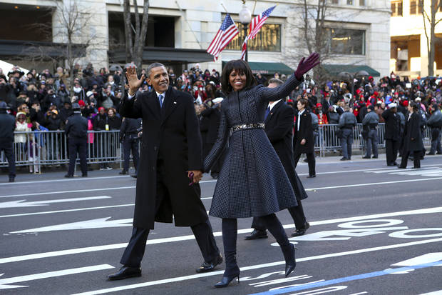 President Barack Obama and first lady Michelle Obama wave as they walk down Pennsylvania Avenue in Washington, Monday, Jan. 21, 2013, during the inaugural parade route , after his ceremonial swearing-in on Capitol Hill during the 57th Presidential Inauguration. (AP Photo/New York Times, Doug Mills, Pool)  ORG XMIT: NYNYT208