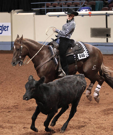 Shayla Mitchell of Cuba, Mo., and her horse, High Skippin Cat, keep a calf from getting away while competing in the boxing event Saturday at the American Quarter Horse Youth Association's world championship at State Fair Park. PHOTO BY JIM BECKEL, THE OKLAHOMAN <strong>Jim Beckel</strong>