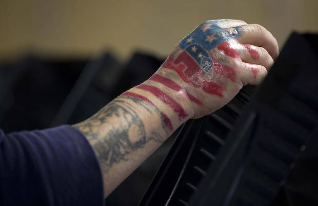 "A brand new tattoo showing his choice of political party is seen on the right hand of Victor ""The Snake Mann"" Wolder as he votes on Election Day, Tuesday, Nov. 6, 2012, in Las Vegas. (AP Photo/Julie Jacobson)"