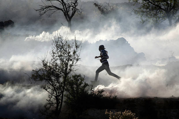 A Palestinian demonstrator runs through a cloud of tear gas during clashes against Israel's operations in Gaza Strip, outside Ofer, an Israeli military prison near the West Bank city of Ramallah, Thursday, Nov. 15, 2012. Meanwhile, Palestinian President Mahmoud Abbas cut short a trip to Europe to deal with the crisis. (AP Photo/Majdi Mohammed) ORG XMIT: JRL138